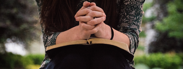 Woman praying with Bible open